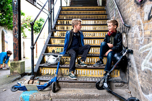 Twins talking on metal staircase - CUF47813