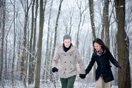 Young couple walking hand in hand in snow covered forest, Ontario, Canada - CUF47822