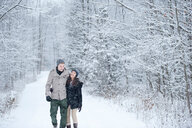 Romantic young couple strolling in snowy forest, Ontario, Canada - CUF47825