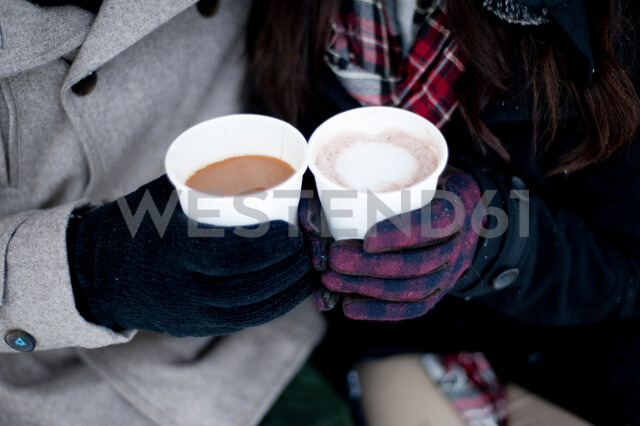 Young couple in winter gloves holding takeaway drinks, close up of hands - CUF47831