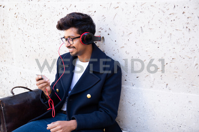 Businessman listening to MP3 with headphones - CUF47837