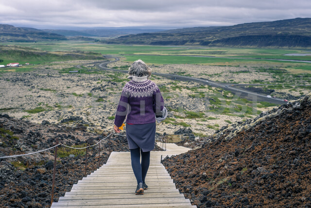Woman walking around Grabrok volcano, Iceland - CUF47855