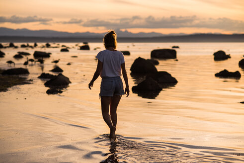 Young woman ankle deep in water at sunset, Quadra Island, Campbell River, Canada - CUF47861