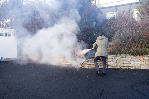 Man extinguishing cable fire in garden near the house - NDF00853