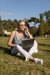 Young woman sitting in park using cell phone and laptop - MAUF02299