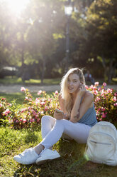 Portrait of smiling young woman sitting in park with cell phone and earbuds - MAUF02308