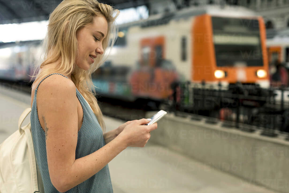 Smiling young woman using cell phone at the train station - MAUF02314 - Mauro Grigollo/Westend61