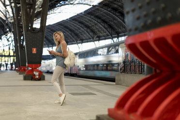 Young woman using cell phone at the train station - MAUF02317