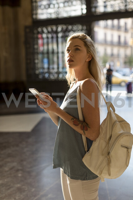 Young woman with cell phone and backpack in the city - MAUF02320 - Mauro Grigollo/Westend61