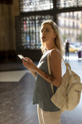 Young woman with cell phone and backpack in the city - MAUF02320
