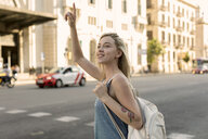 Smiling young woman in the city hailing a taxi - MAUF02323