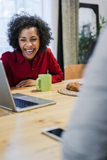 Laughing woman with laptop at table - GIOF05481