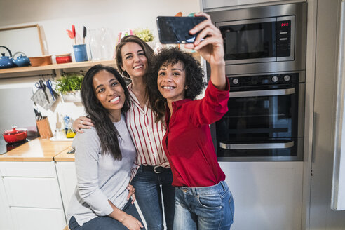 Three happy women posing for a selfie in kitchen - GIOF05487