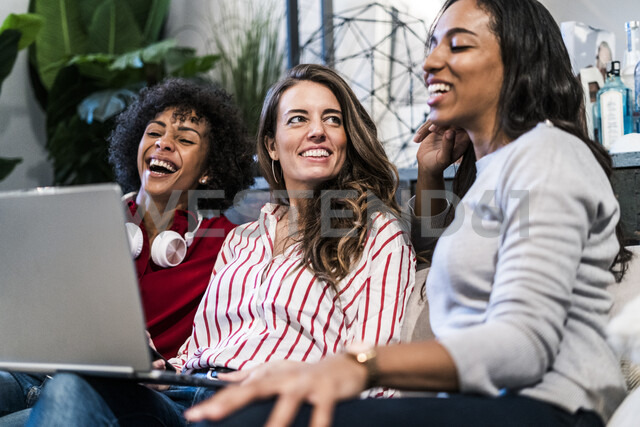 Three happy women with laptop sitting on couch - GIOF05505