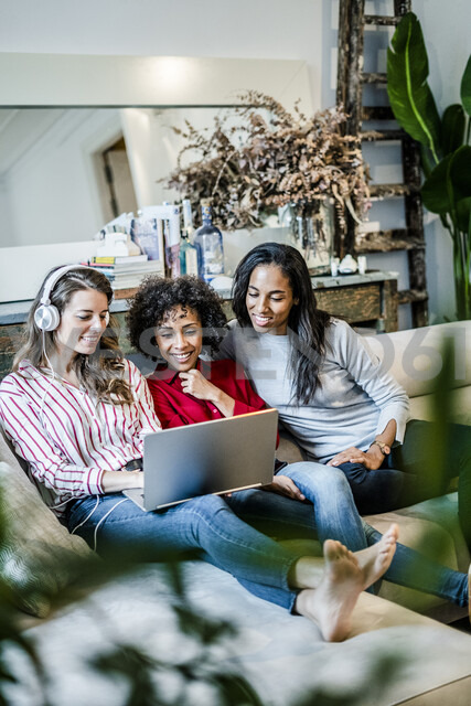 Three happy women with laptop sitting on couch - GIOF05511 - Giorgio Fochesato/Westend61
