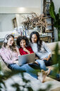 Three happy women with laptop sitting on couch - GIOF05511