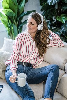 Smiling woman with cup of coffee and headphones sitting on couch - GIOF05514