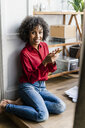 Portrait of smiling woman sitting on the floor at home with cell phone - GIOF05523