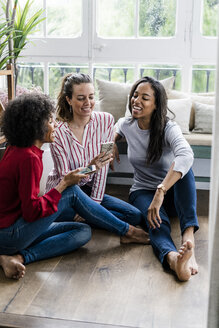 Three happy women sitting on the floor at home with cell phones - GIOF05526