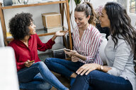 Three happy women sitting on the floor at home with cell phones - GIOF05529