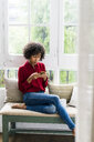 Serious woman sitting at the window at home using cell phone - GIOF05535