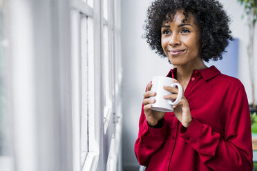 Smiling woman with cup of coffee looking out of window at home - GIOF05538