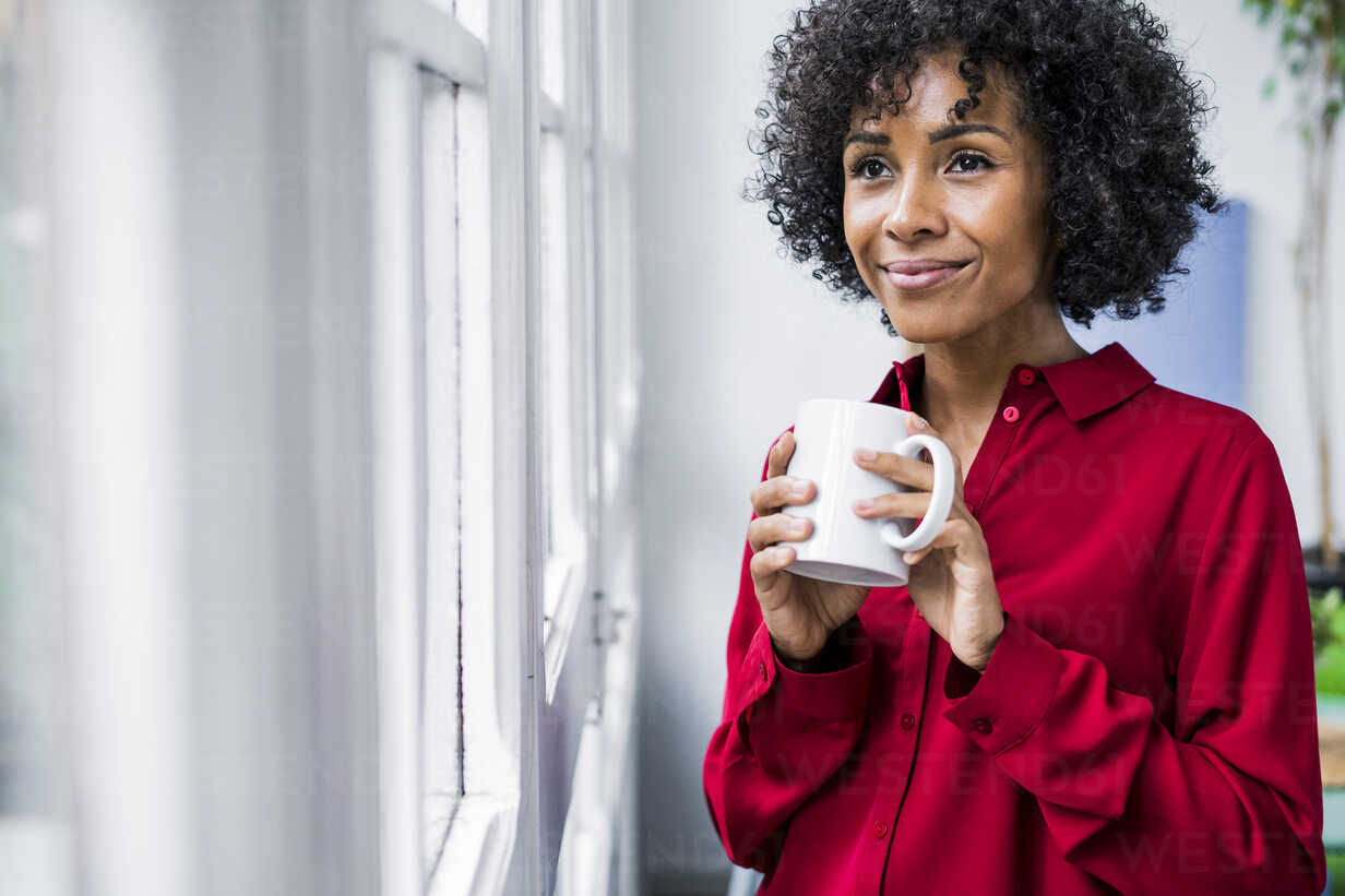 Smiling woman with cup of coffee looking out of window at home - GIOF05538 - Giorgio Fochesato/Westend61
