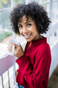 Portrait of smiling woman with cup of coffee at the window at home - GIOF05541