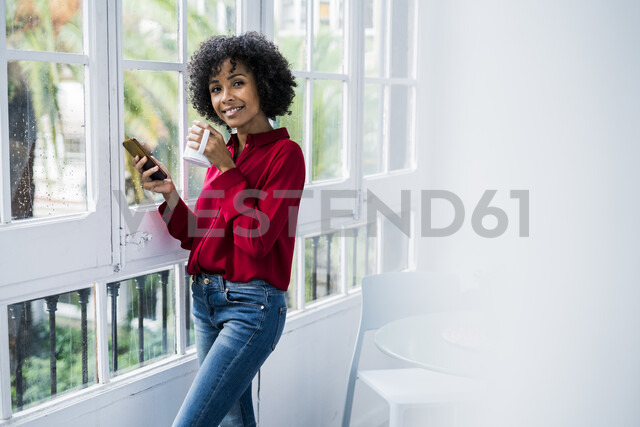 Portrait of smiling woman with cup of coffee and cell phone standing at the window at home - GIOF05544 - Giorgio Fochesato/Westend61