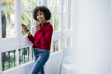 Portrait of smiling woman with cup of coffee and cell phone standing at the window at home - GIOF05544