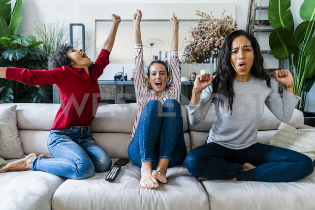 Three excited women on couch at home watching Tv and cheering - GIOF05547