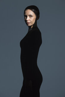 Portrait of slim woman dressed in black with flare on her face - VGF00185