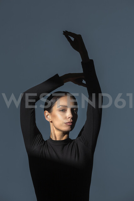 Portrait of woman dressed in black with flare on her face doing stretching exercise - VGF00191