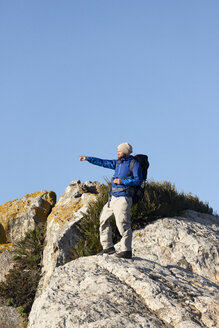 Spain, Andalusia, Tarifa, man on a hiking trip standing on rock pointing his finger - KBF00415
