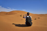 Morocco, man with backpack sitting on desert dune taking picture with smartphone - EPF00548