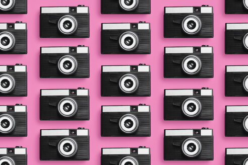 Classic plastic photo cameras organized in a row over pink background - DRBF00127