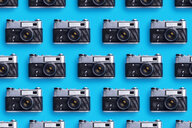 Classic photo cameras organized in a row over blue background - DRBF00130
