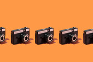 Classic plastic photo cameras organized in a row over orange background - DRBF00133