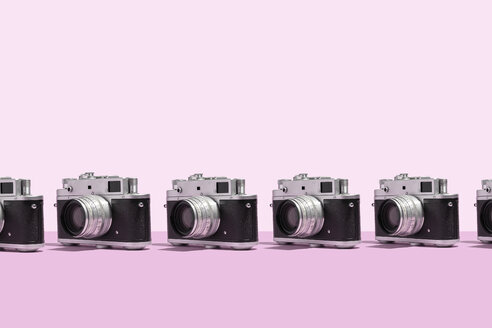 Photo cameras organized in a row over pink background - DRBF00136