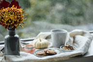 Cup of coffee, cookies and autumnal decoration on window sill - JESF00197