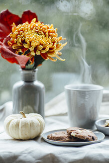 Cup of steaming coffee, cookies and autumnal decoration on window sill - JESF00200