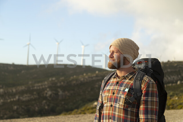Spain, Andalusia, Tarifa, smiling man on a hiking trip with wind turbines in background - KBF00441
