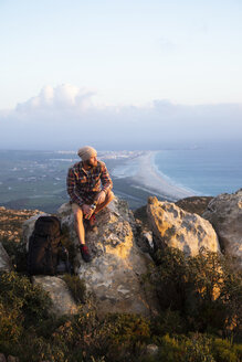 Spain, Andalusia, Tarifa, man on a hiking trip at the coast sitting on rock - KBF00453