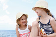 Two girls in sun hats eating sandwiches on beach, Scopello, Sicily, Italy - CUF47899