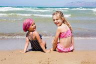 Two girls sitting on beach looking back, portrait, Castellammare del Golfo, Sicily, Italy - CUF47902