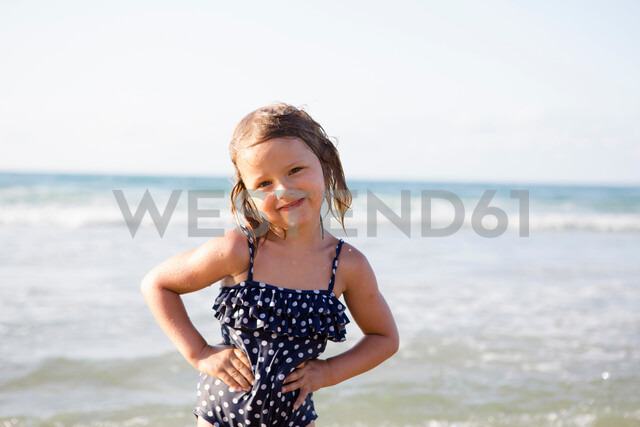 Cute girl on beach in spotted swimming costume, portrait, Castellammare del Golfo, Sicily, Italy - CUF47905
