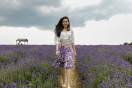 Mid adult woman with long brown hair strolling through lavender field, portrait - CUF47908