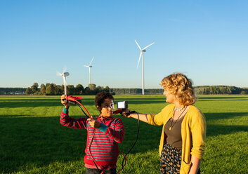 Teenage boy and girl experimenting with sustainable energy by wind turbines, Netherlands - CUF47914