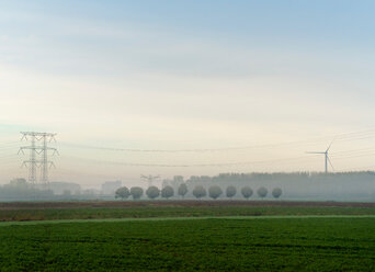 Landscape with wind turbine and power lines on a foggy morning, Netherlands - CUF47917