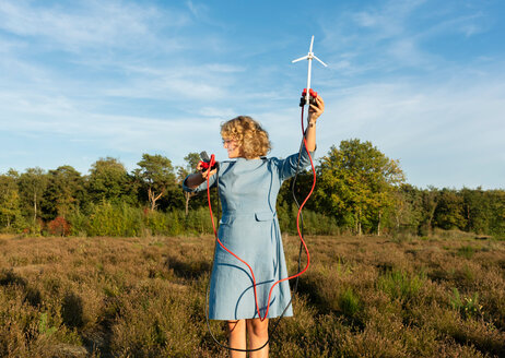 Teenage girl powering LED light using miniature wind turbine, Netherlands - CUF47935